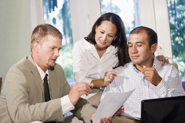 Hispanic couple at home with financial advisor reviewing chart