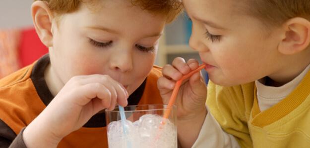 Children sharing a milkshake
