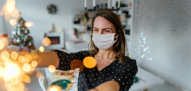 Masked woman decorating for the holidays